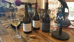 La Crema wine bottles and Radio Misfits microphone on table